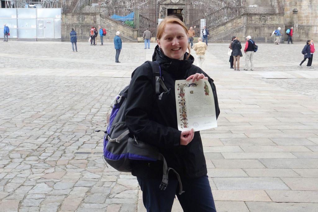 Mit der Pilgerurkunde Compostela vor der Kathedrale in Santiago.